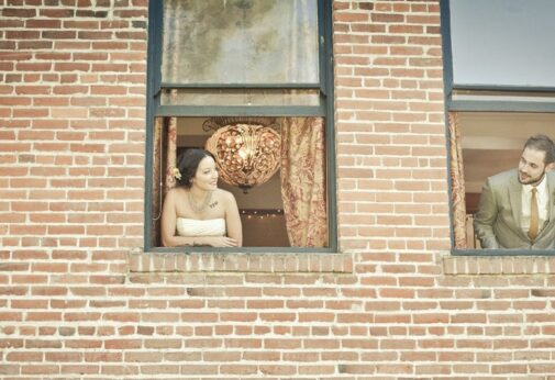 Bride and groom leaning out of windows at the Balch Hotel